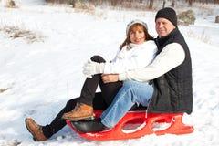 Les aînés couplent sur le traîneau en parc d'hiver Image stock