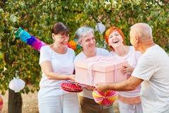 Les aînés félicitent leur ami avec un cadeau Photo libre de droits