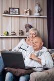 Les aînés heureux couplent la lecture de l'ordinateur portable dans la chambre confortable ; Image stock