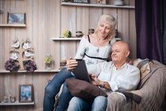 Les aînés heureux couplent la lecture du comprimé dans la chambre confortable ; Photographie stock