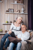 Les aînés heureux couplent la lecture du comprimé dans la chambre confortable ; Images libres de droits