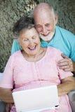 Les aînés se connectent à Netbook Photographie stock