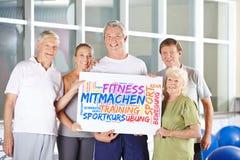 Les aînés tiennent l'affiche au centre de fitness photos stock
