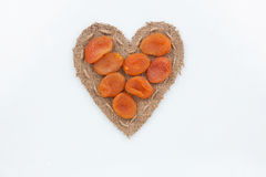Les abricots secs se trouve au coeur fait de toile de jute Photos libres de droits