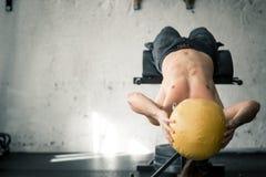 Les ABS de exécution d'homme sportif puissant s'exercent avec le medicine-ball image libre de droits
