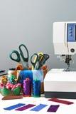 Les accessoires de couture dans un panier et les bobines des fils à côté de cousent Images stock