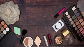 Les accessoires de la femme et composer et les produits de beauté sur le fond en bois banque de vidéos
