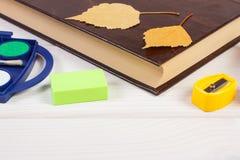 Les accessoires de livre et d'école sur les conseils blancs, de nouveau au concept d'école, copient l'espace pour le texte Image stock