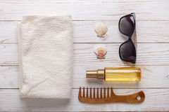 Les accessoires de mer sur le fond en bois bronzent l'huile, peigne, serviette, coquillages, lunettes de soleil image stock