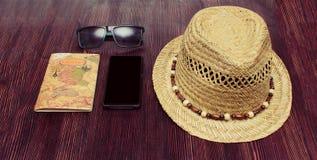 Les accessoires de voyage téléphonent, chapeau, les lunettes de soleil, passeport sur le fond en bois photos libres de droits