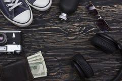 Les accessoires des hommes : portefeuille, écouteurs, lunettes de soleil, parfum, appareil-photo et espadrilles Photos stock