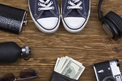 Les accessoires des hommes : portefeuille, écouteurs, lunettes de soleil, parfum, appareil-photo et espadrilles Photo stock