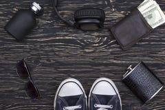 Les accessoires des hommes : portefeuille, écouteurs, lunettes de soleil, parfum, flacon et espadrilles Image stock