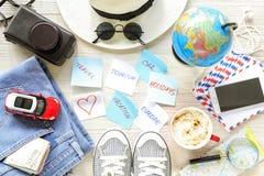Les accessoires du ` s de voyageur et les articles, autocollants avec des notes sur le fond en bois blanc, des vacances de planif Photos stock