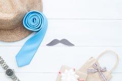 Les accessoires jour du ` s de père, de ` heureux s d'homme et le cadeau mettent en sac sur le bois blanc Images libres de droits