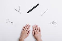 Les accessoires pour la manucure se trouvent autour des mains d'une femelle sur un blanc merci images stock