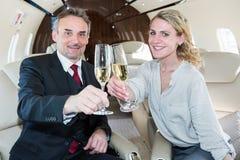 Les acclamations font tinter l'équipe d'affaires en verre dans un jet d'entreprise buvant c Photographie stock
