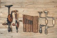 Les accolades de foret avec le peu dans l'outil en cuir roulent sur un workbenc en bois Images stock