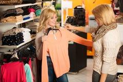 Les achats de la femme - deux filles dans un choo de boutique de vêtements Photos stock