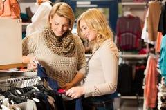 Les achats de la femme - deux filles dans un choo de boutique de vêtements Photo libre de droits