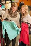 Les achats de la femme - deux filles dans une boutique de vêtements choisissant le vêtement Image libre de droits