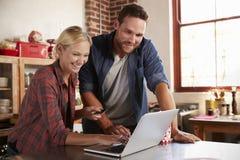 Les achats en ligne de jeunes couples blancs dans la cuisine, se ferment  Photo libre de droits