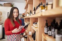 Les achats femelles de client en cosm?tiques ind?pendants stockent comparer des prix utilisant le t?l?phone portable images stock