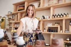 Les achats femelles de client en cosm?tiques ind?pendants stockent comparer des prix utilisant le t?l?phone portable images libres de droits