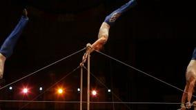 Les acrobates exécutent des exercices sur la barre dans l'arène de cirque banque de vidéos