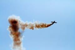 Les acrobaties aériennes surfacent dans le nuage de la fumée Image libre de droits