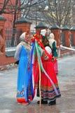 Les acteurs de rue dans des costumes nationaux colorés se tiennent sur la rue Photo libre de droits