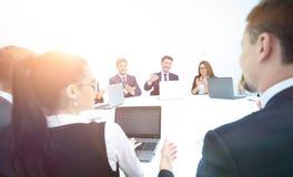 Les actionnaires regardent aux ordinateurs portables et se renseignent sur le développement Image stock