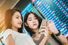 Les adolescentes asiatiques utilisent un smartphone au vol de contrôle Photographie stock