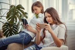 Les adolescentes avec l'ordinateur de PC de comprimé et la musique de écoute d'écouteurs et communiquent dans les réseaux sociaux image libre de droits