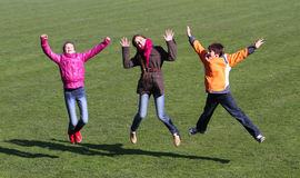 Les adolescentes et le garçon apprécient à sauter Image libre de droits