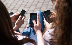 Les adolescentes heureuses textotant l'amusement hawing de sms passent le temps ensemble en parc de ville Photos stock