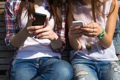 Les adolescentes heureuses textotant l'amusement hawing de sms passent le temps ensemble en parc de ville Photographie stock