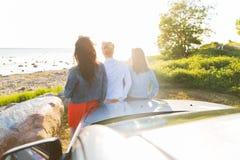 Les adolescentes ou les femmes heureuses s'approchent de la voiture au bord de la mer Image stock