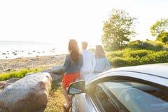 Les adolescentes ou les femmes heureuses s'approchent de la voiture au bord de la mer Images stock