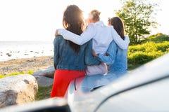 Les adolescentes ou les femmes heureuses s'approchent de la voiture au bord de la mer Photographie stock