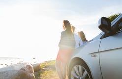 Les adolescentes ou les femmes heureuses s'approchent de la voiture au bord de la mer Photos libres de droits