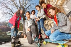 Les adolescents avec des planches à roulettes ou fait du roller Image libre de droits
