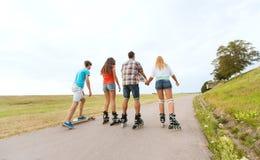 Les adolescents avec fait du roller et des longboards Image libre de droits