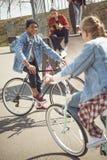 Les adolescents ayant l'amusement et montant des bicyclettes en planche à roulettes se garent Image stock