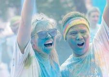 Les adolescents couverts de couleur époussettent les bras rasing dans le ciel Photographie stock libre de droits