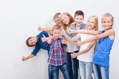 Les adolescents de sourire montrant correct se connectent le blanc Photos libres de droits