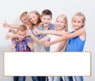 Les adolescents de sourire montrant correct se connectent le blanc Photos stock