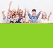 Les adolescents de sourire montrant correct se connectent le blanc Image stock