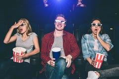 Les adolescents effrayés et inquiétés sont reposants et observants le film Les filles essayent de ne pas voir quel ` s allant sur Images stock