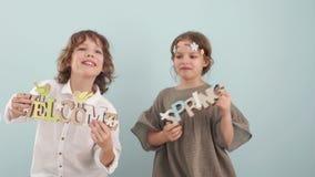 Les adolescents frère et la danse de soeur avec le ressort signe dedans leurs mains Décor de Pâques, paysage de ressort, Joyeuses clips vidéos